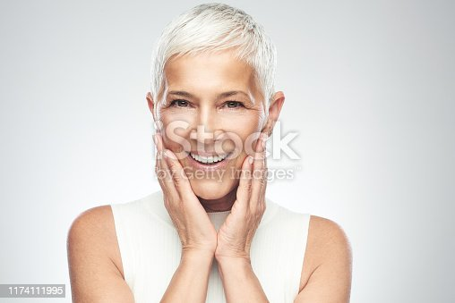 Beautiful smiling senior woman with short gray hair posing in front of gray background. Beauty photography.