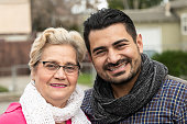 Smiling hispanic senior woman posing with her mid adult son looking at the camera