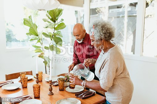 Senior woman pouring water in glass from jug at home. Retired couple is arranging dining table in room. They are preparing together.