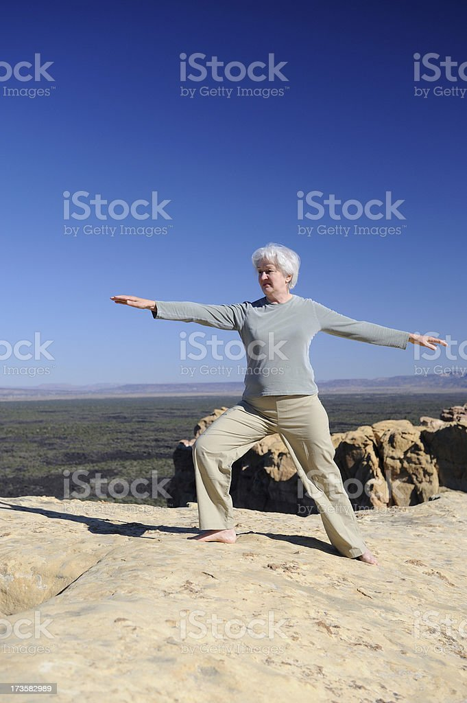 Senior Woman Practicing Tai Chi near Cliff Edge stock photo