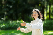 Senior Asian woman (60s) practicing Tai Chi.