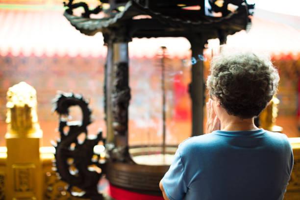 senior woman praying buddha at temple stock photo