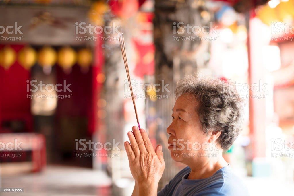 senior woman praying buddha with incense stick at temple stock photo