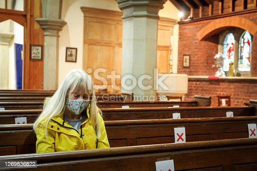 istock Senior woman praying in church wearing protective face mask 1269836822