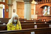 istock Senior woman praying in church wearing protective face mask 1269836822