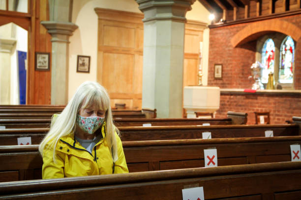 Senior woman praying in church wearing protective face mask Color image depicting a senior woman in her 70s sitting alone in a church while wearing a protective face mask. The pews are mark with ticks and crosses to delineate a social distancing system during the covid-19 pandemic. Room for copy space. place of worship stock pictures, royalty-free photos & images