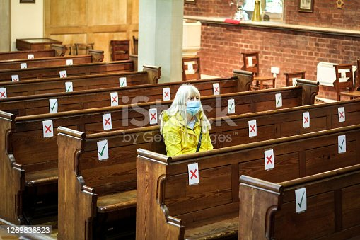 istock Senior woman praying in church wearing protective face mask 1269836823