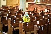 istock Senior woman praying in church wearing protective face mask 1269836823