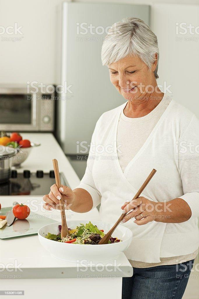 Senior woman preparing food in kitchen royalty-free stock photo