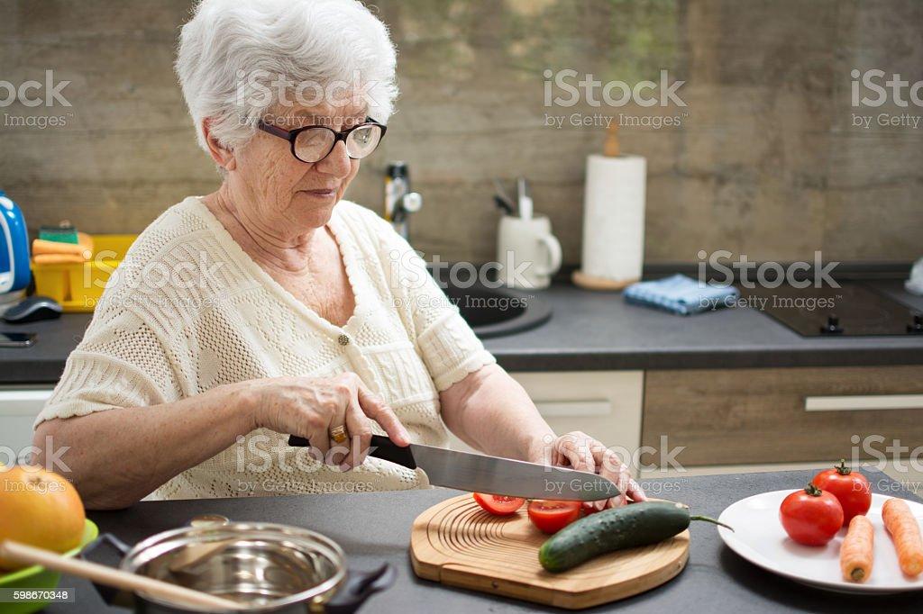Senior woman preparing healthy food from fresh vegetables in kitchen. - foto de stock