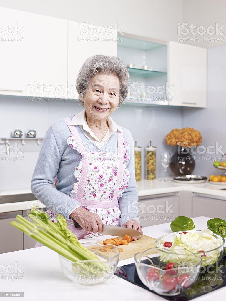 senior woman preparing meal in kitchen stock photo
