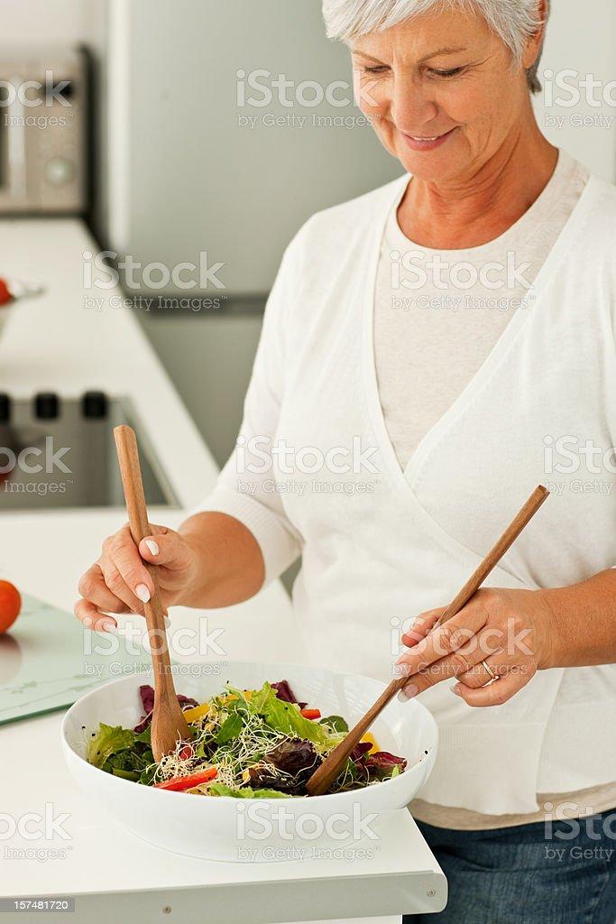 Senior woman preparing salad in kitchen royalty-free stock photo