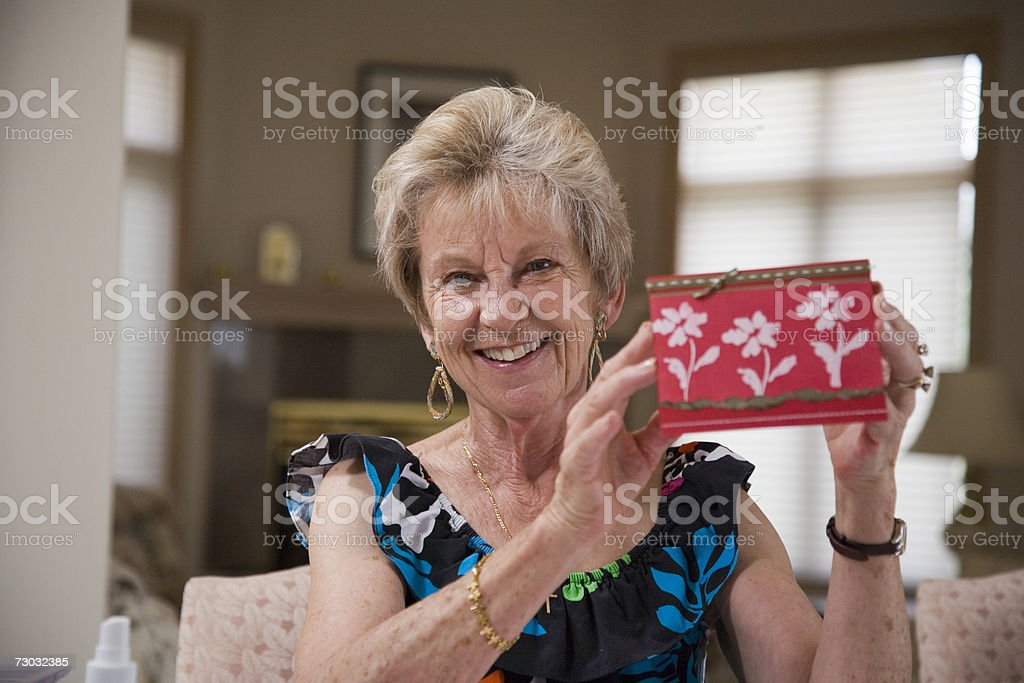 Senior woman presenting homemade greeting card at home, portrait foto de stock royalty-free