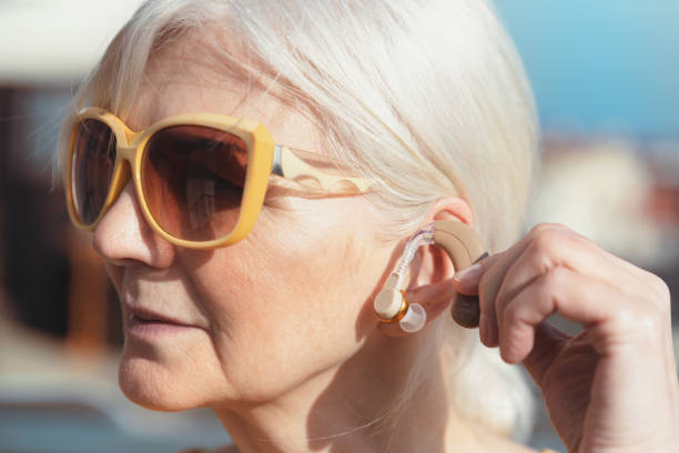 senior woman puts on the hearing aid - hearing loss stock pictures, royalty-free photos & images