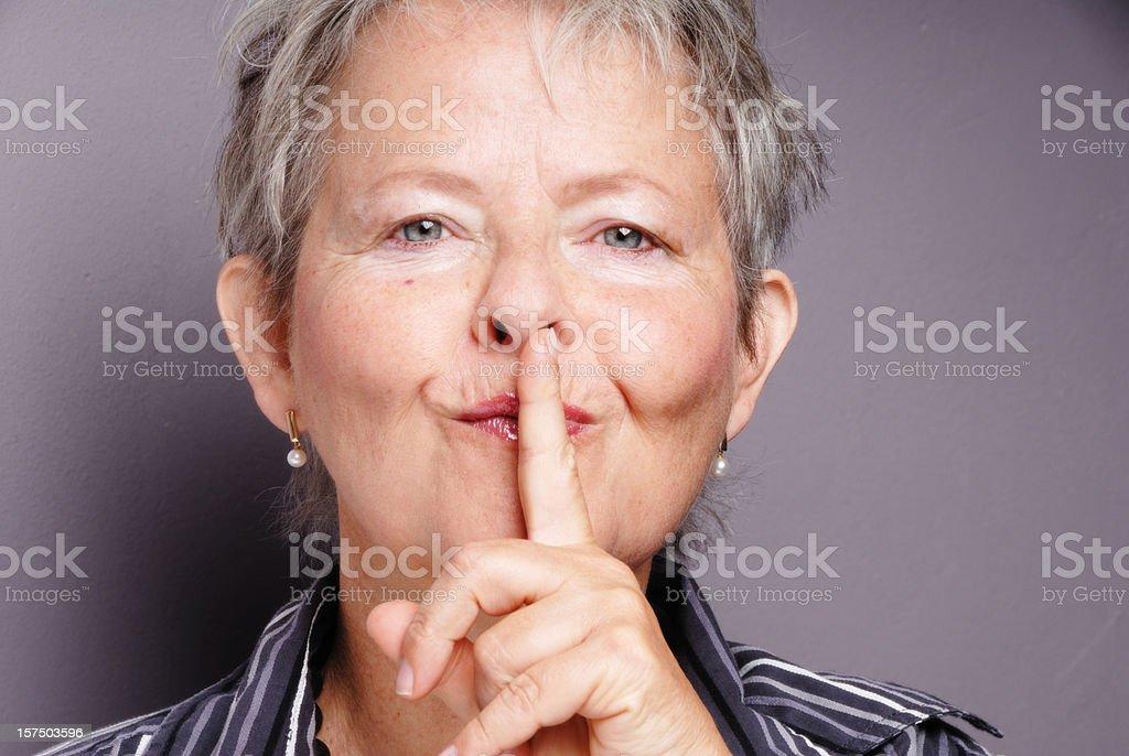 senior woman putting finger on lips royalty-free stock photo
