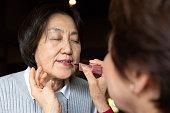 年配の女性は彼女の友人に化粧を置く