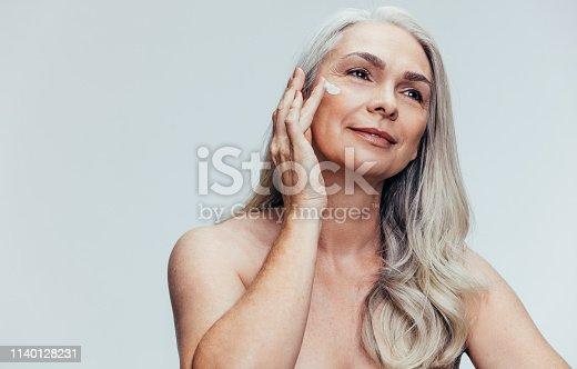 istock Senior woman putting on anti aging cream 1140128231