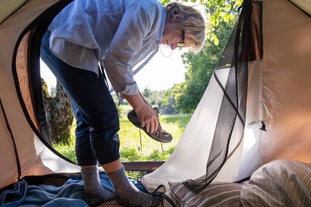 senior frau auf ihre bergschuhe, morgen in-out zeltblick - zelt stehhöhe stock-fotos und bilder