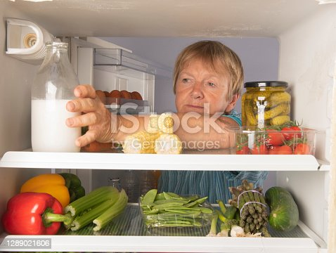Senior woman reaching into a fridge full of healthy foods at home