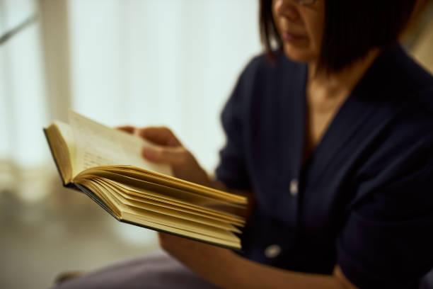 先輩女性は紙で作られた本を読む - books ストックフォトと画像