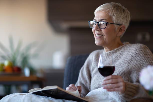 Senior woman reading a book at home stock photo