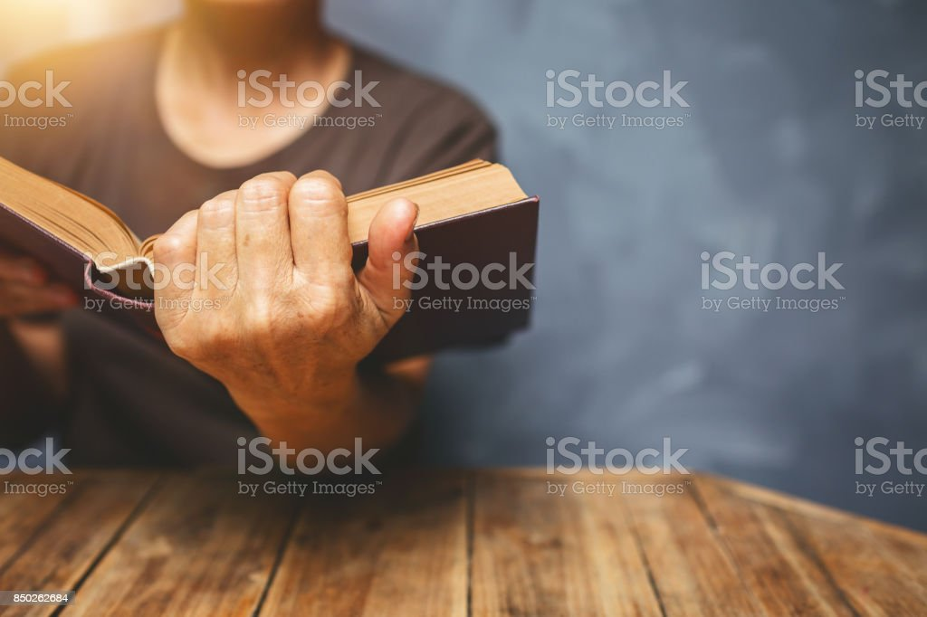 Senior woman reading a book at living room with old vintage table and concrete wall background. stock photo