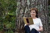 Portrait of Pretty Senior Woman Reading a Book Under the Tree in a Garden