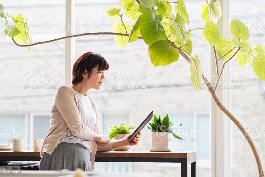 Senior woman reading a digital tablet stock photo
