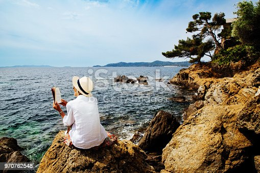 Senior woman reading a book on a rocky seashore in Provence, France.