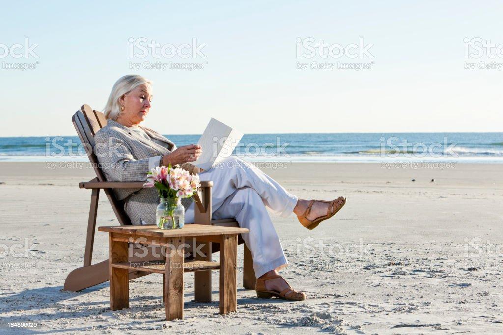 Senior woman reading book on beach stock photo