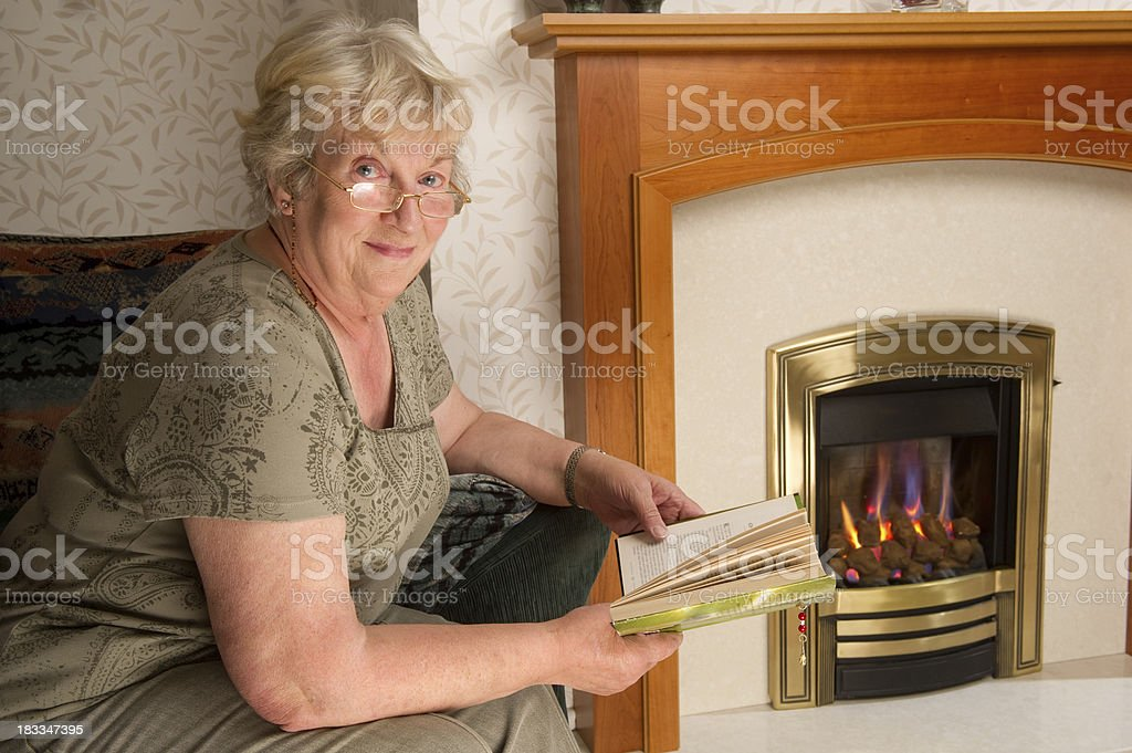 Senior Woman Reading by the Fireplace royalty-free stock photo