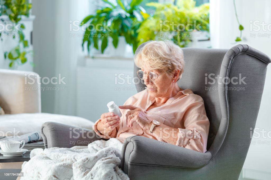 An elderly lady sitting in an armchair covered with blanket, holding...