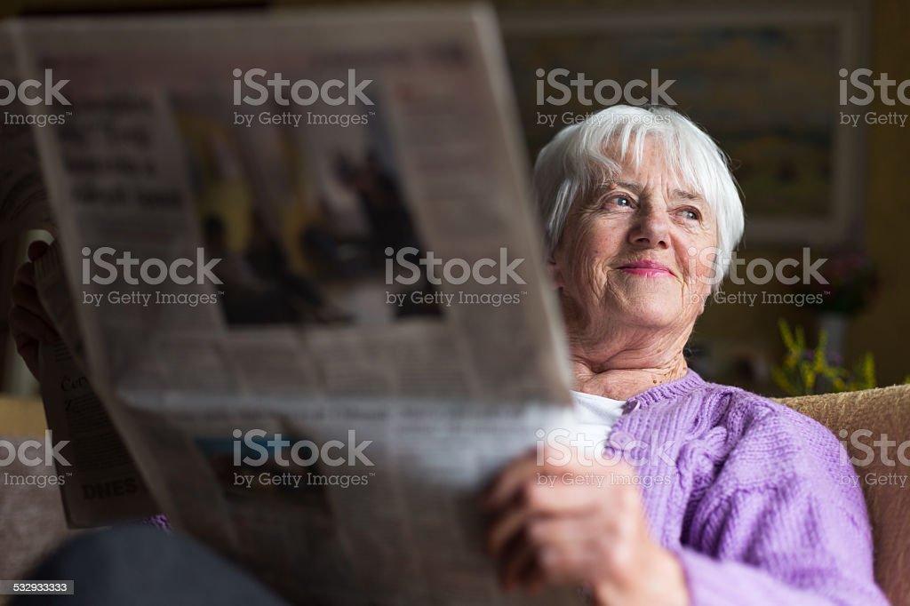 Senior woman reading morning newspaper stock photo