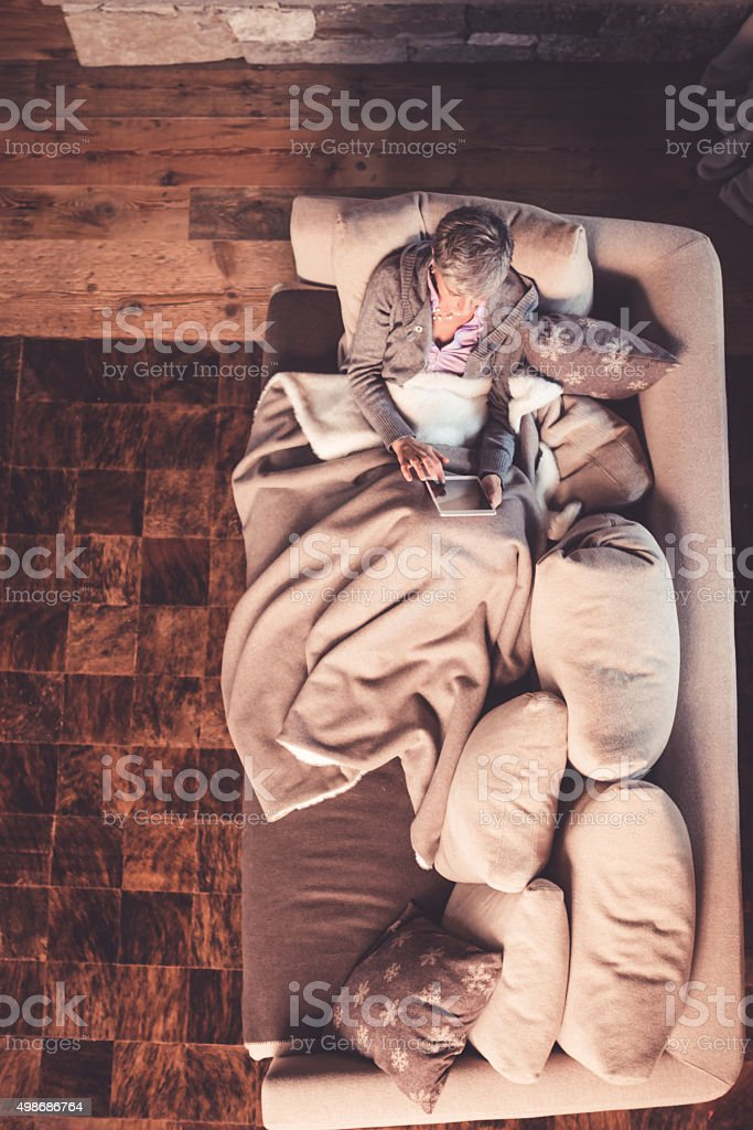 Senior Woman Reading on Sofa stock photo