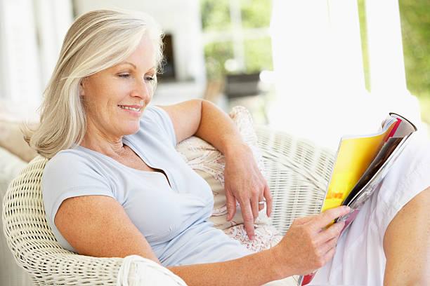 Senior woman reading outside stock photo