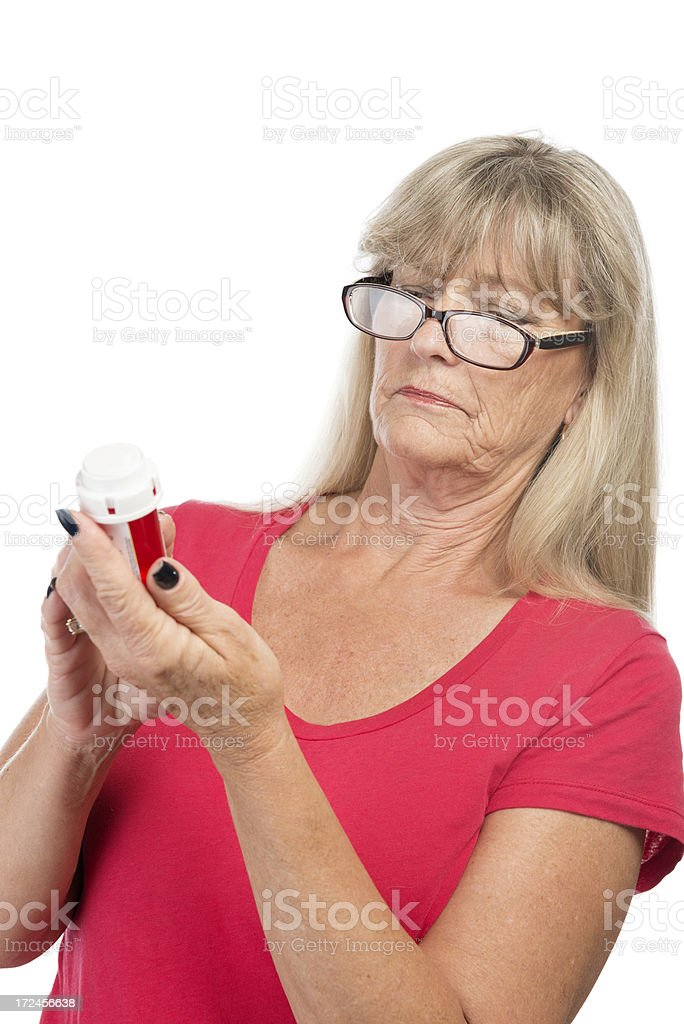 Senior woman reading pill bottle. royalty-free stock photo