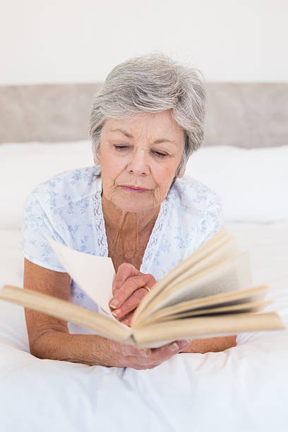 senior woman reading geschichte buch im bett - kurzgeschichten stock-fotos und bilder