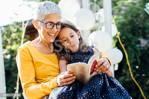 Old woman reading a book to her granddaughter when relaxing on a swing