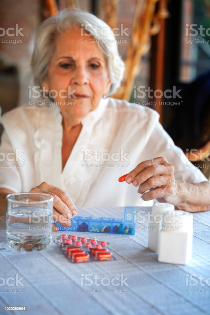 Health Themes. Senior woman ready to grabbing a capsule from daily...