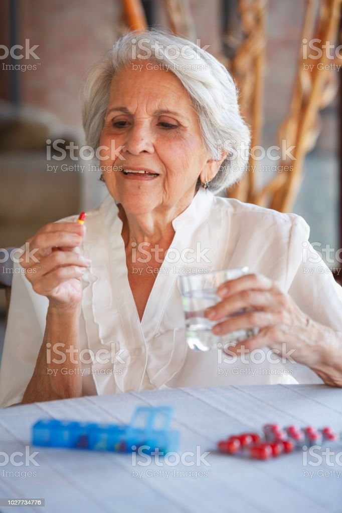 Health Themes. Senior woman ready to taking a pill at home with...