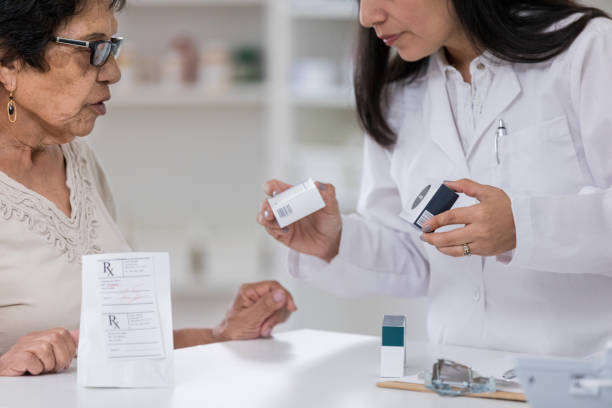 Senior woman receives multiple prescriptions at pharmacy Senior woman discusses medication with pharmacist. The pharmacist is filling several prescriptions for the woman. generic drug stock pictures, royalty-free photos & images