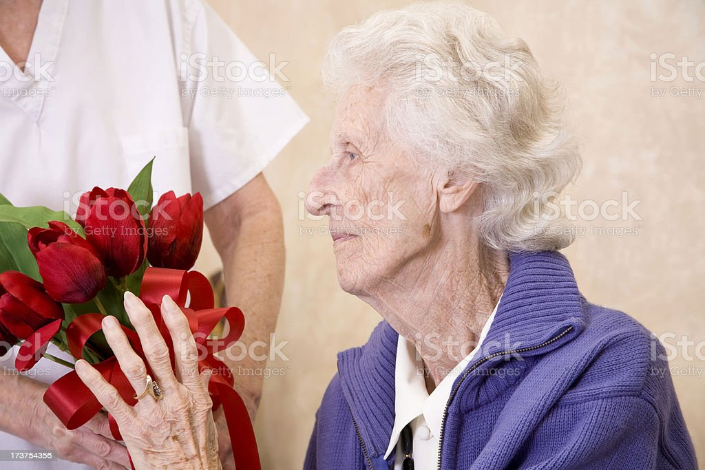 Senior woman receiving bouquet red flowers from medical staff. Valentine's. royalty-free stock photo