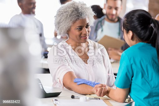 Beautiful senior African American female patient prepares to receive a flu vaccine at a free medical clinic.