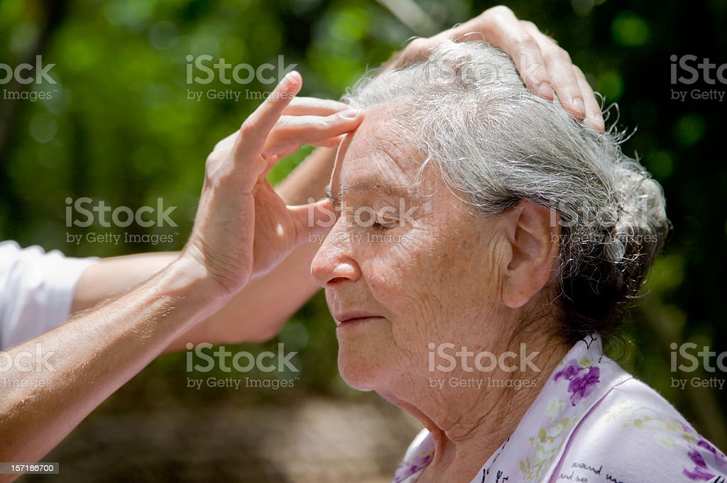 Senior woman receiving head massage outdoors royalty-free stock photo