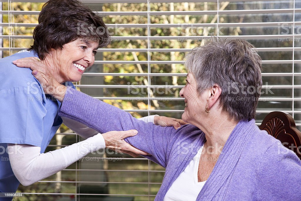 Senior woman receiving home physical therapy. Therapist. Healthcare worker. royalty-free stock photo