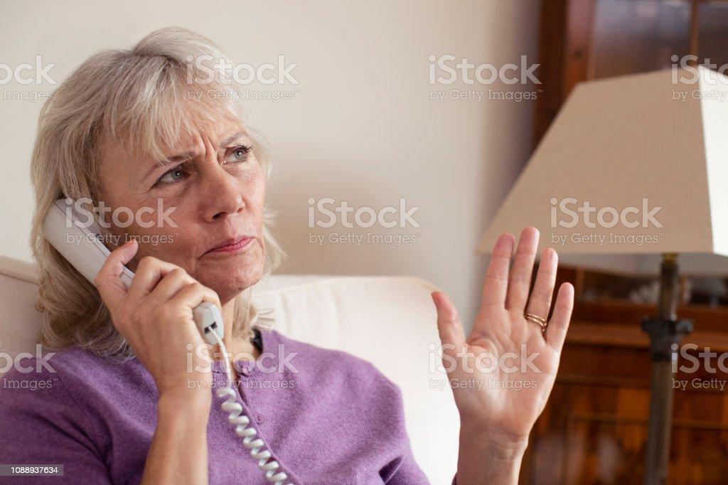Mujer Senior recibiendo llamadas no deseadas en casa foto de stock libre de derechos
