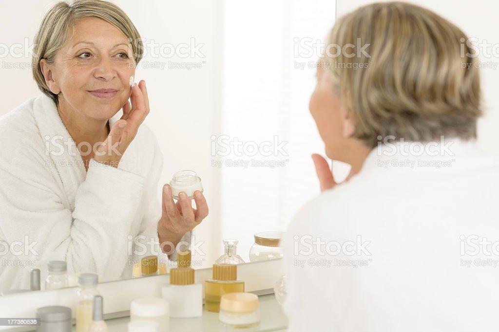 Senior woman reflection in bathroom mirror stock photo
