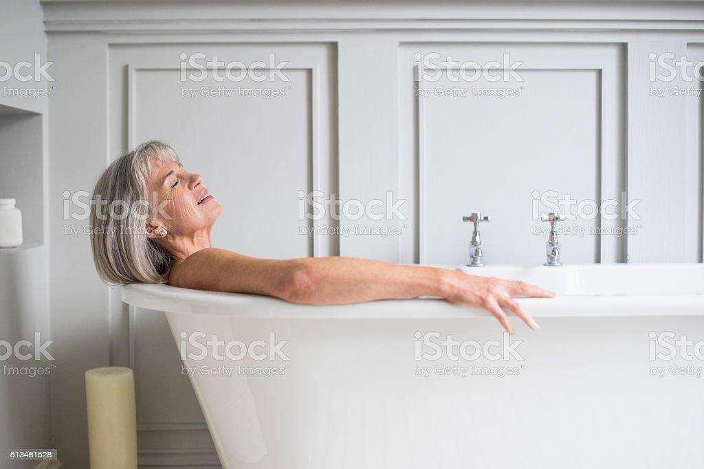Senior woman relaxing in bath with eyes closed stok fotoğrafı