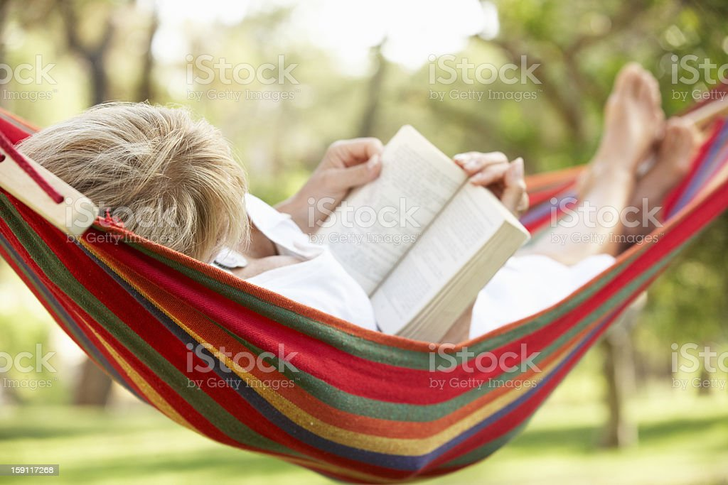 Senior Woman Relaxing In Hammock With Book stock photo