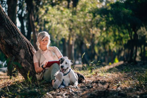 Senior mujer relajante en la naturaleza con libro y mascota perro - foto de stock